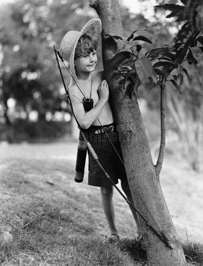 Мальчик за деревом с луком и стрелы (все показанные люди более длинные живущие и никакое имущество не существует Гарантии поставщ стоковые фотографии rf