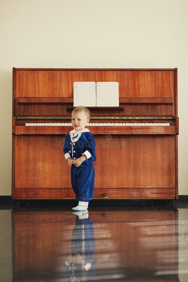 Мальчик играет рояль стоковая фотография