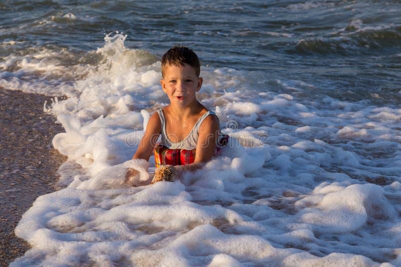 Мальчик играя в прибое моря стоковое фото