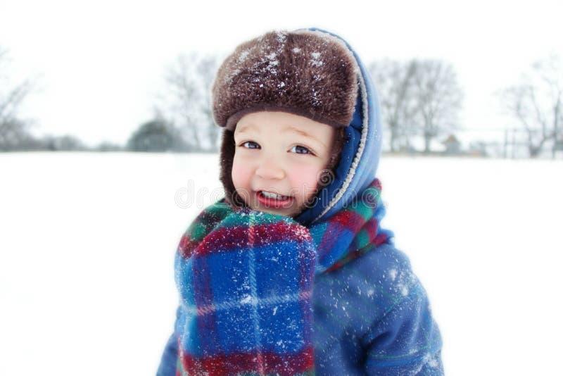 Мальчик играя в снеге стоковое изображение