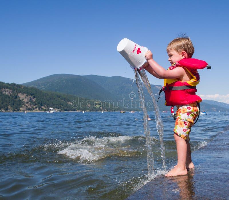 Мальчик играя на озере стоковое изображение rf