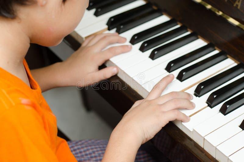 Мальчик играя рояль дома стоковые фотографии rf