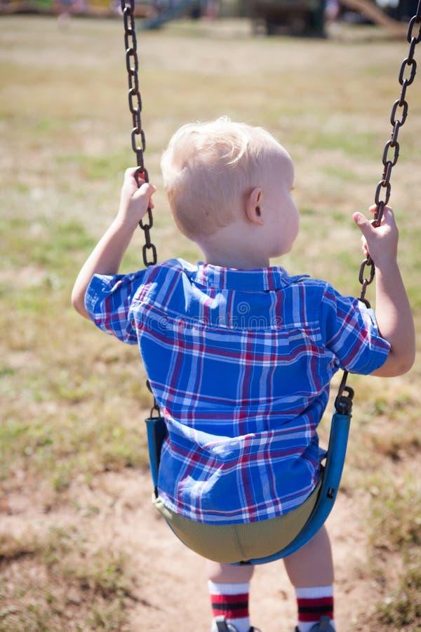 Мальчик играя снаружи на Swingset стоковые фото