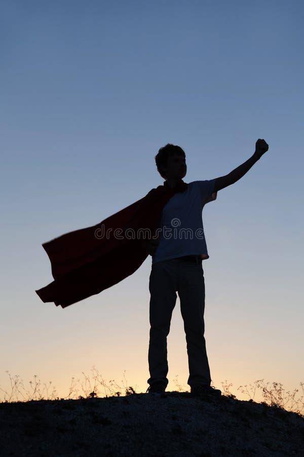 Мальчик играя супергероев на предпосылке неба, силуэте тройника стоковое изображение rf
