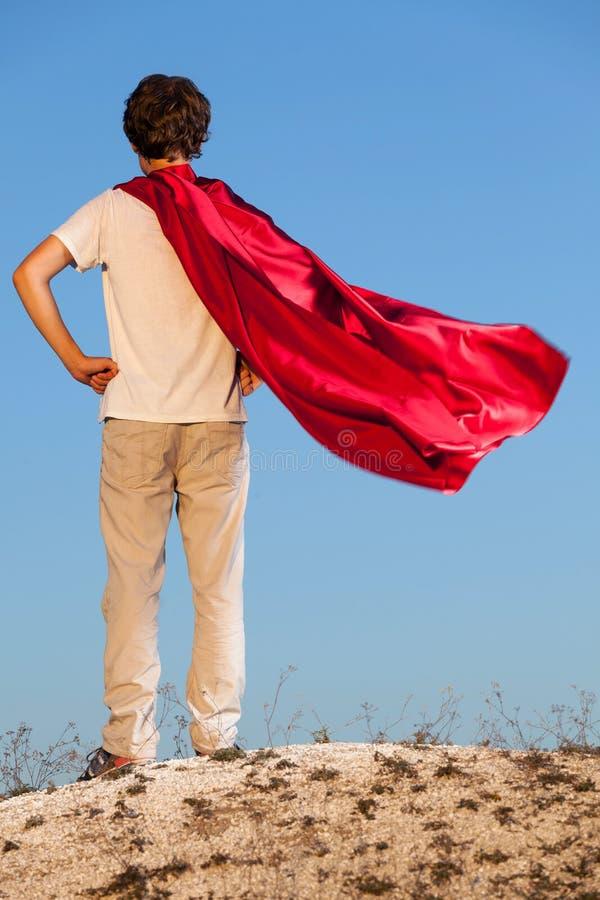 Мальчик играя супергероев на предпосылке неба, стоковая фотография