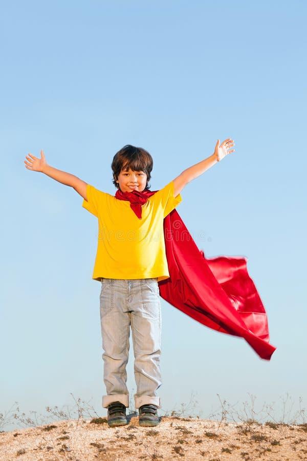 Мальчик играя супергероев на backgrounde неба стоковые изображения rf