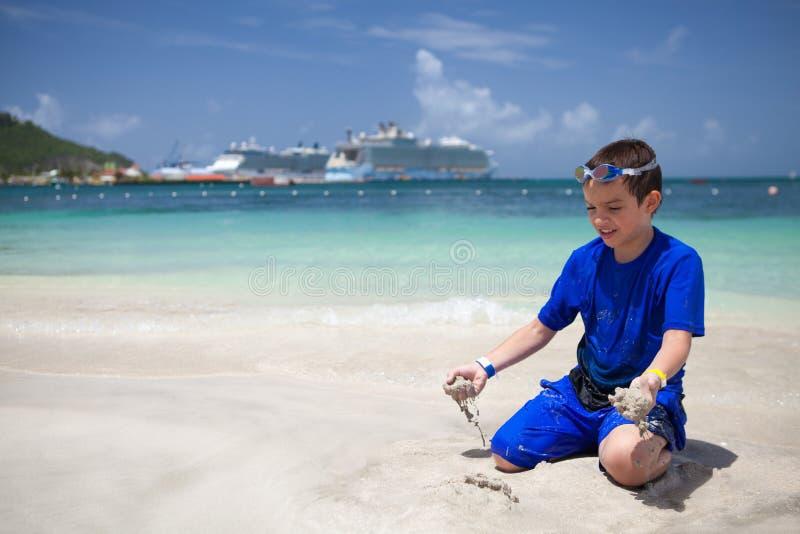 Мальчик играя с песком на пляже стоковые изображения rf