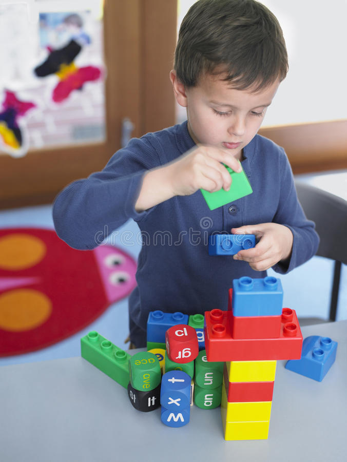 Мальчик играя с строительными блоками в классе стоковые фотографии rf