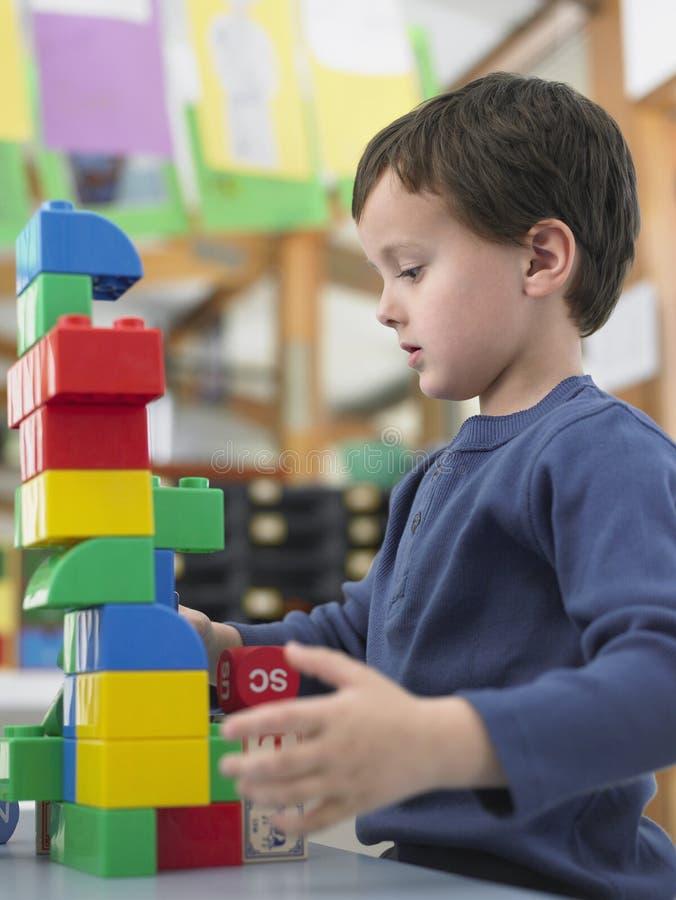 Мальчик играя с строительными блоками в классе стоковые фото