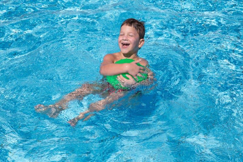 Мальчик играя с шариком в бассейне стоковые фотографии rf