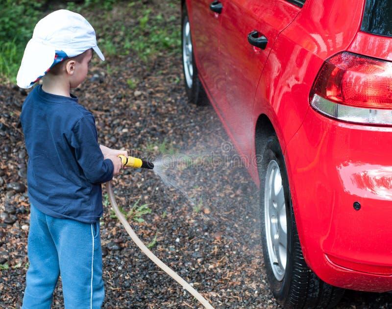 Мальчик играя с шлангом воды, автомобилем мытья стоковая фотография