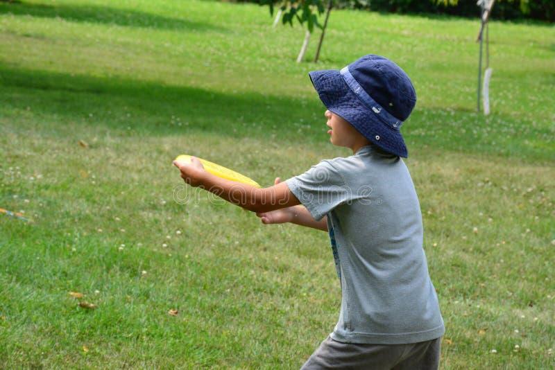 Мальчик играя с Frisbee стоковое изображение rf