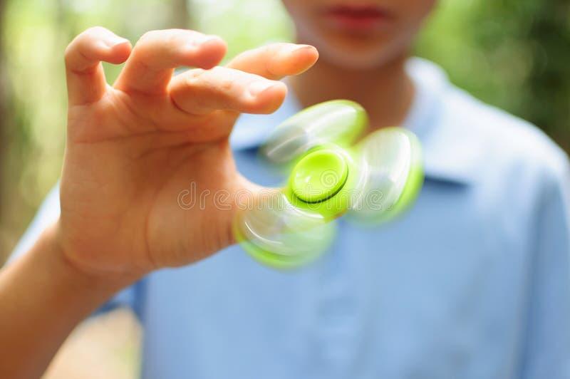 Мальчик играя с Tri обтекателем втулки руки непоседы стоковое изображение rf