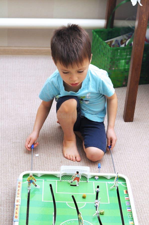 Мальчик играя футбол таблицы стоковые фото