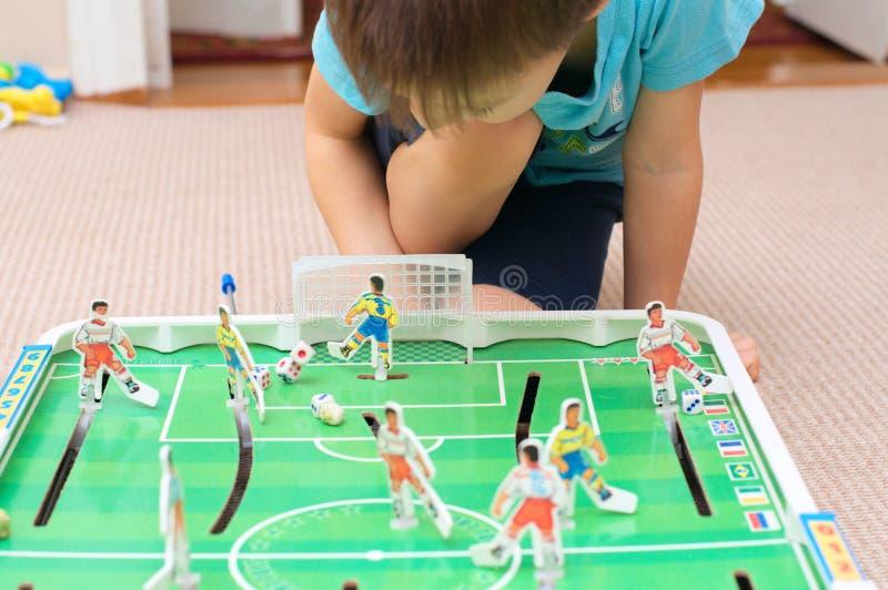 Мальчик играя футбол таблицы стоковое фото rf
