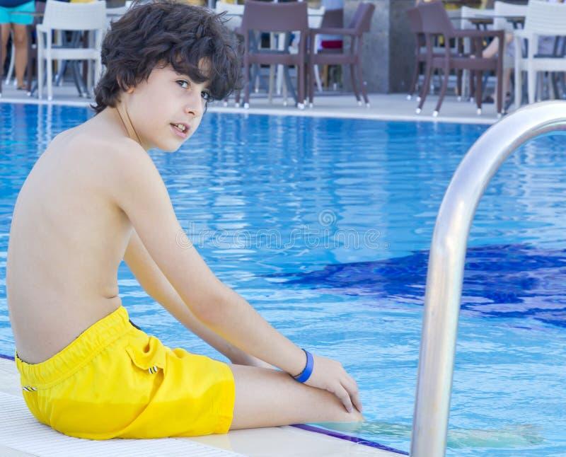 Мальчик имеет потеху в бассейне стоковое фото rf