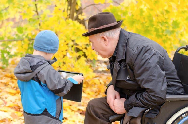 Мальчик используя ПК таблетки с наблюдать деда стоковое фото
