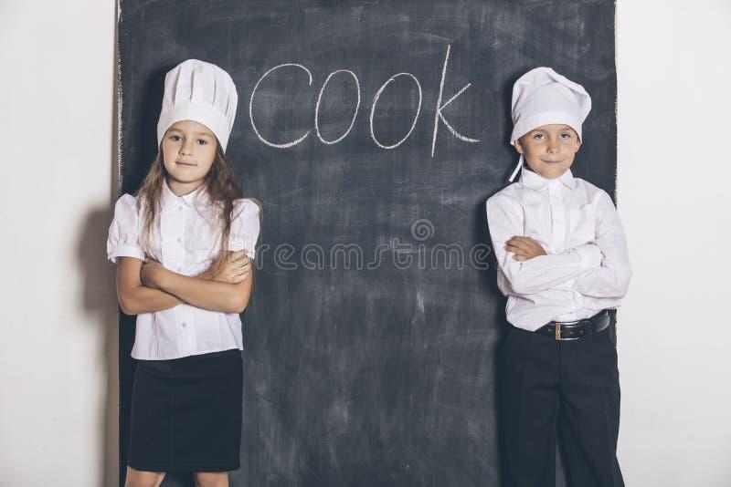 Мальчик и девушка варят с доской шифера под меню текста стоковая фотография rf
