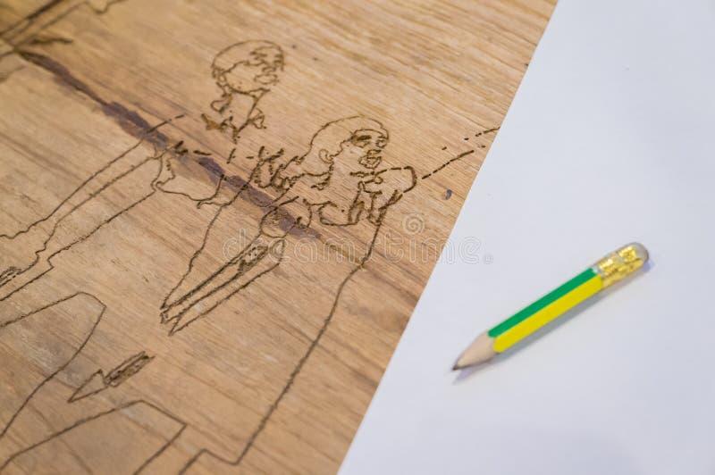 Мальчик и девушка высекая на древесине с карандашем и бумагой стоковые изображения rf