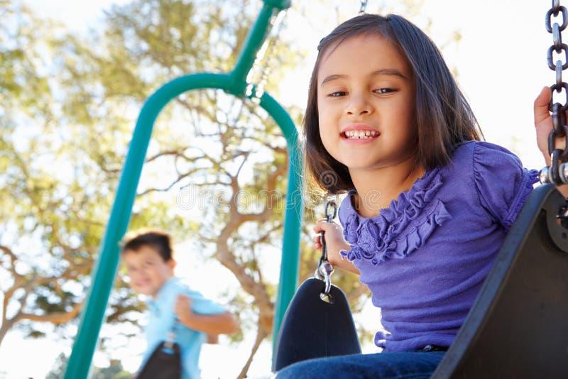 Мальчик и девушка играя на качании в парке стоковое изображение rf