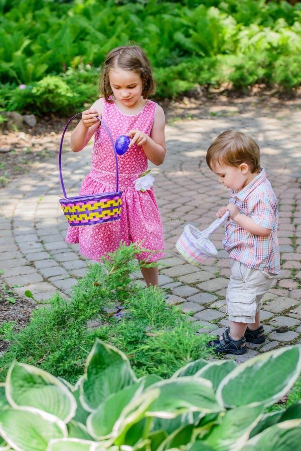 Мальчик и девушка на охоте пасхального яйца стоковое фото