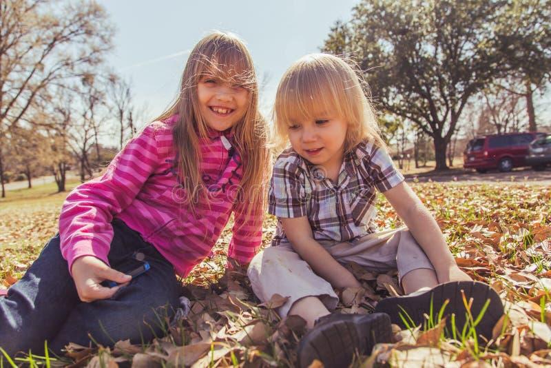 Мальчик и девушка сидя в поле стоковое изображение rf