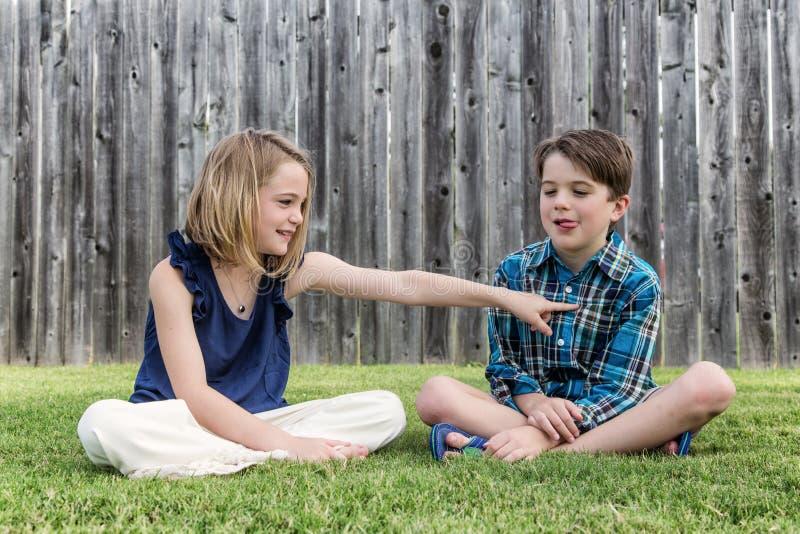 Мальчик и девушка сидя на дворе стоковые изображения