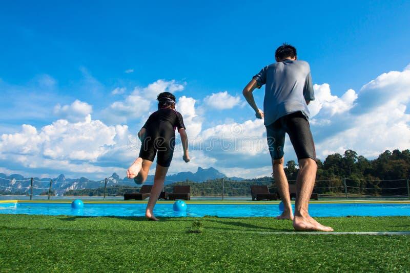 Мальчик и девушка скача в бассейн в озере стоковая фотография rf