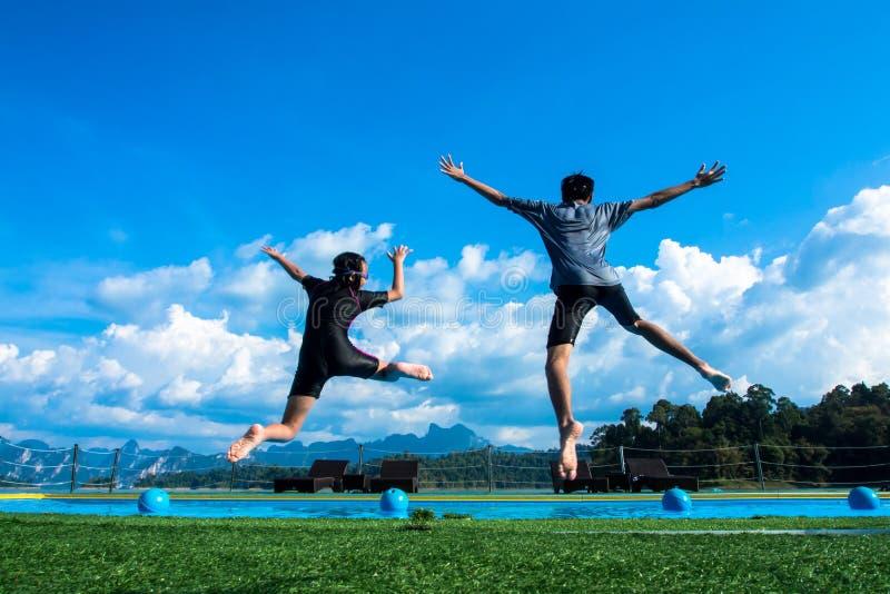 Мальчик и девушка скача в бассейн в озере стоковые фото