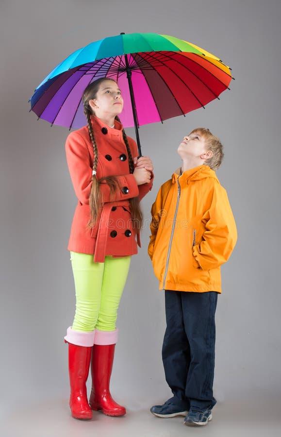 Мальчик и девушка с красочным зонтиком стоковое изображение