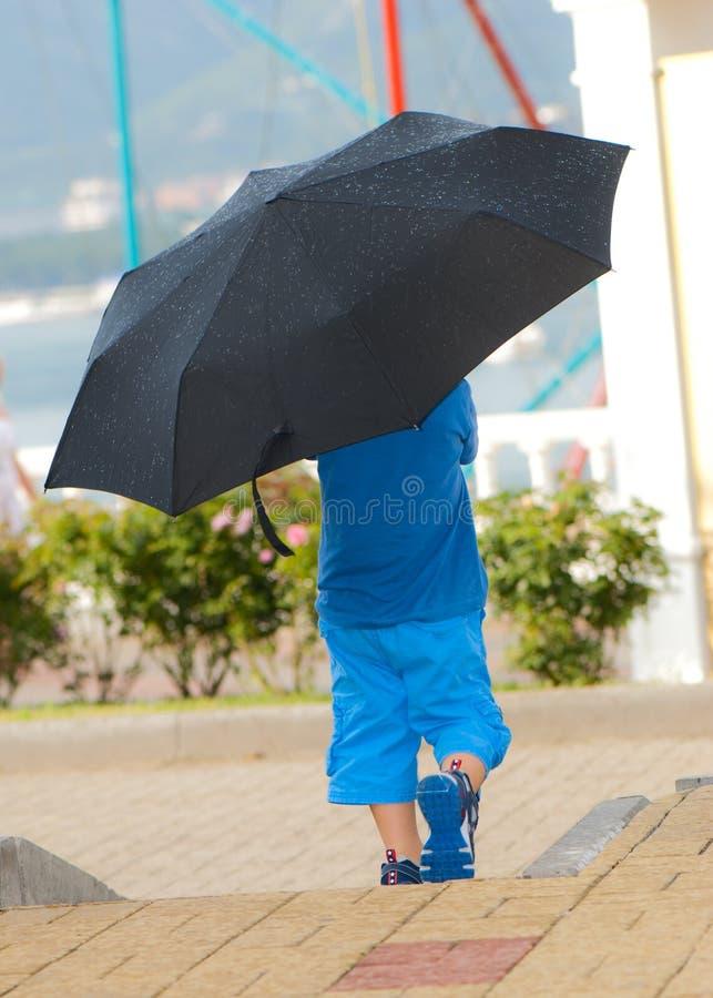 Мальчик идет под зонтик стоковые изображения