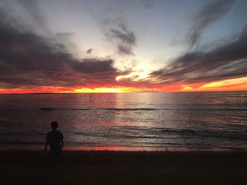 Мальчик и заход солнца стоковая фотография