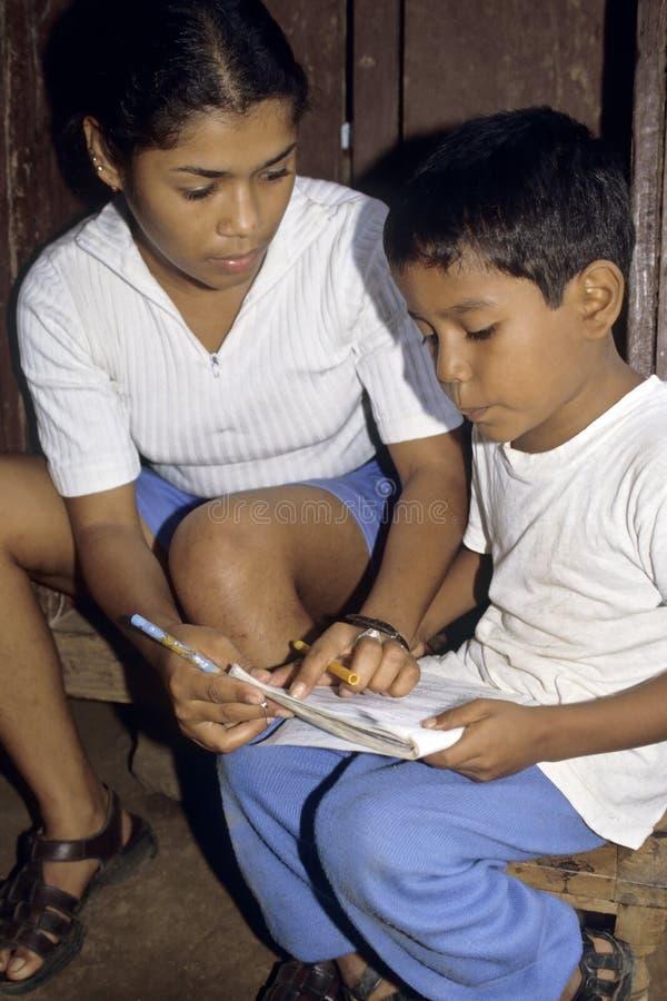 Мальчик и учитель латиноамериканца портрета во время чтения классифицируют стоковое фото