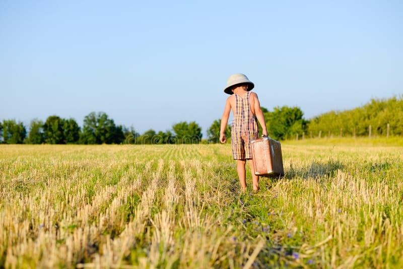 Мальчик идя большой старый чемодан прочь нося стоковые фотографии rf