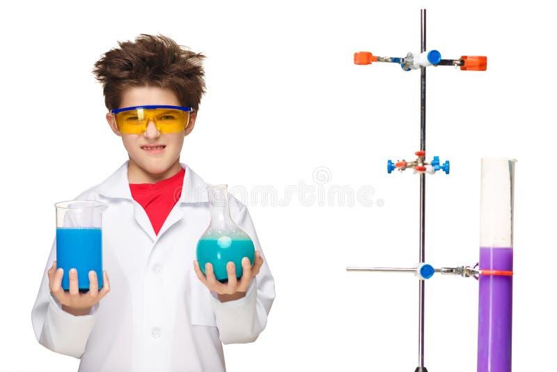 Мальчик как химик делая эксперимент с стоковые изображения