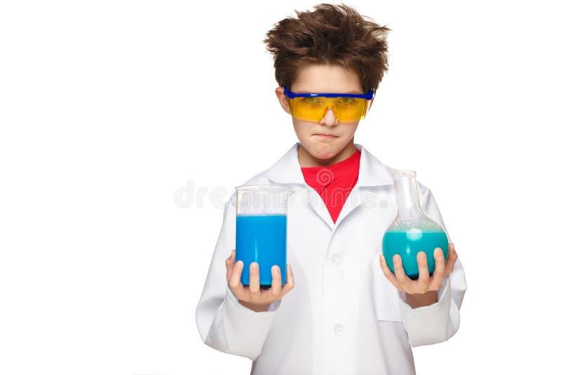 Мальчик как химик делая эксперимент с стоковые фотографии rf