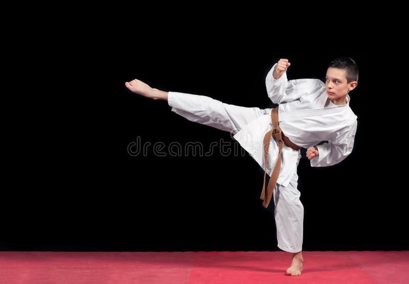 Мальчик карате в белом бой кимоно изолированный на черной предпосылке стоковая фотография