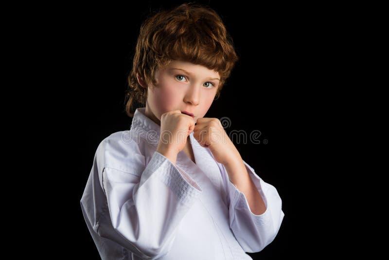 Мальчик карате в белом кимоно изолированном на черноте стоковые изображения