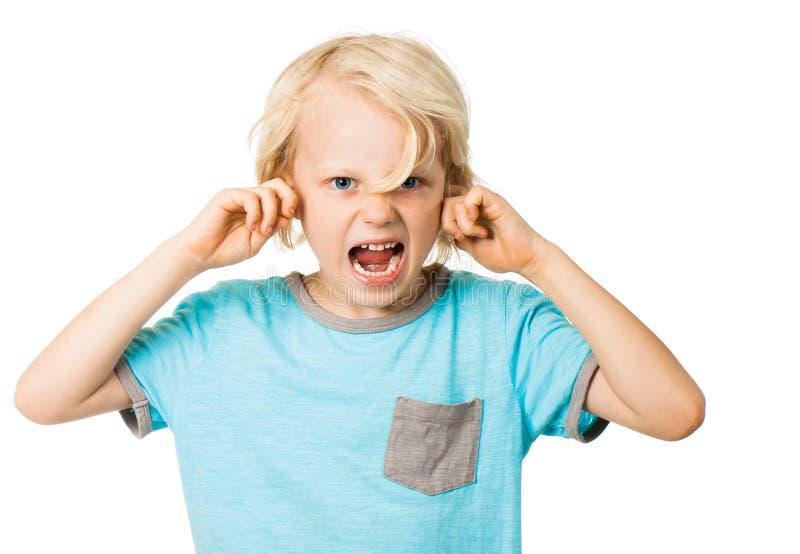 Мальчик кричащий и преграждая уши стоковые фото