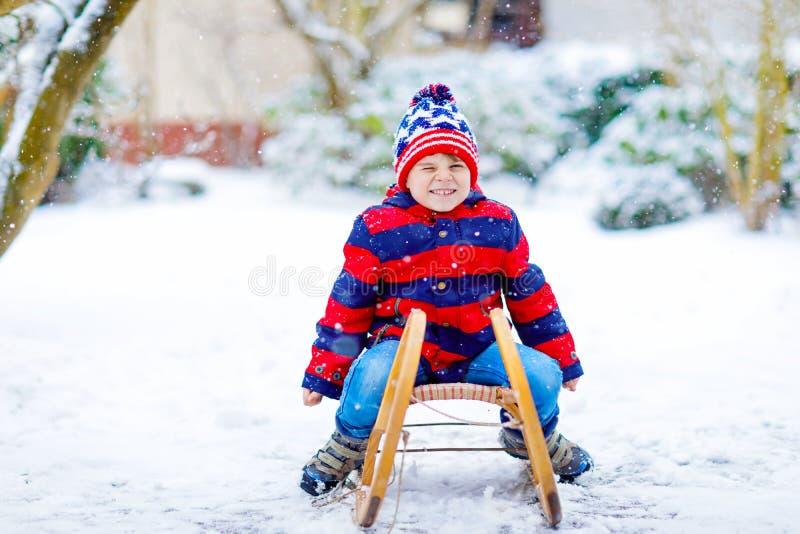 Мальчик маленького ребенка наслаждаясь ездой саней в зиме стоковая фотография rf
