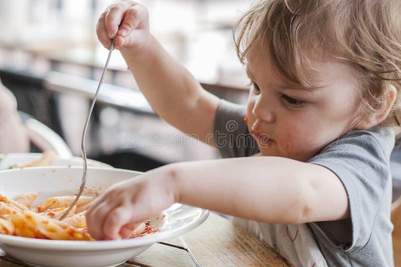 Мальчик малыша есть макаронные изделия стоковые изображения