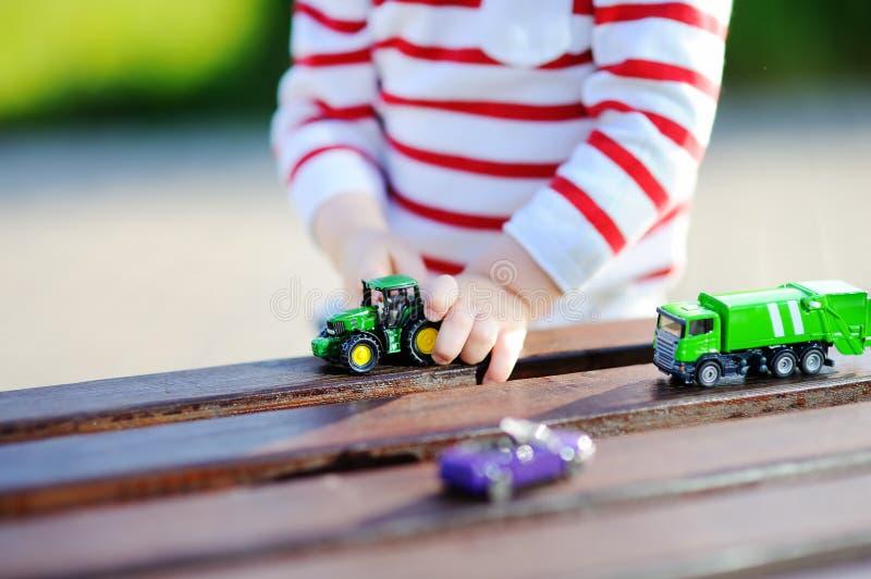 Мальчик малыша играя с автомобилями игрушки близко вверх стоковое фото rf