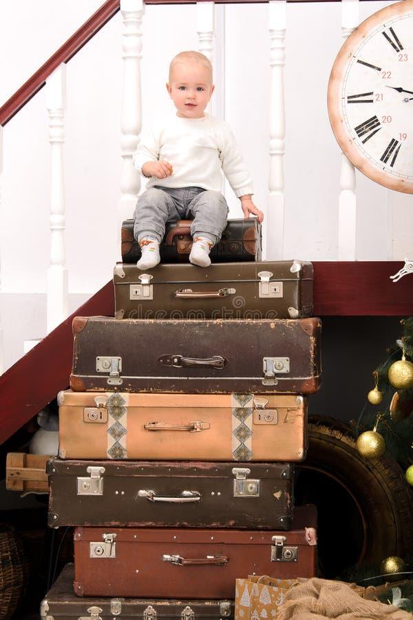 Мальчик малыша на куче чемоданов стоковое изображение rf