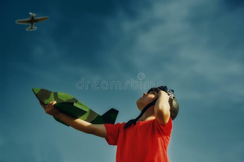 Мальчик мечтает быть пилотом играя с моделью самолета стоковое изображение