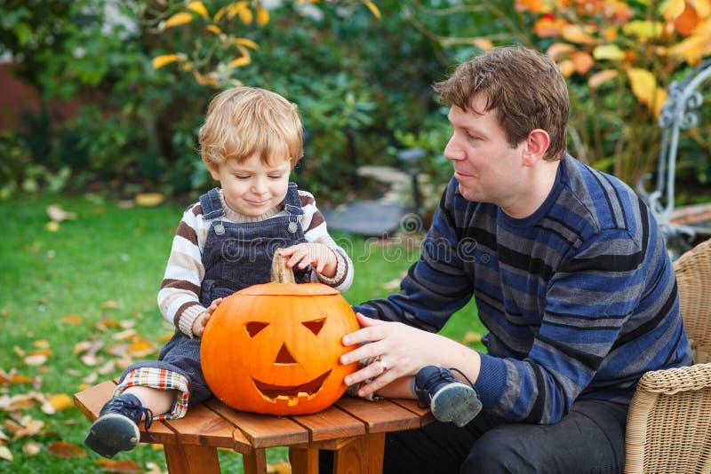 Мальчик молодого человека и малыша делая тыкву хеллоуина стоковые фото