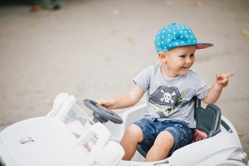 Мальчик моды управляя автомобилем игрушки в парке стоковая фотография