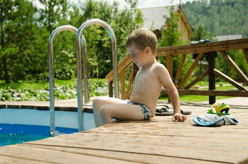 Мальчик наслаждается поплавать в бассейне стоковое фото rf