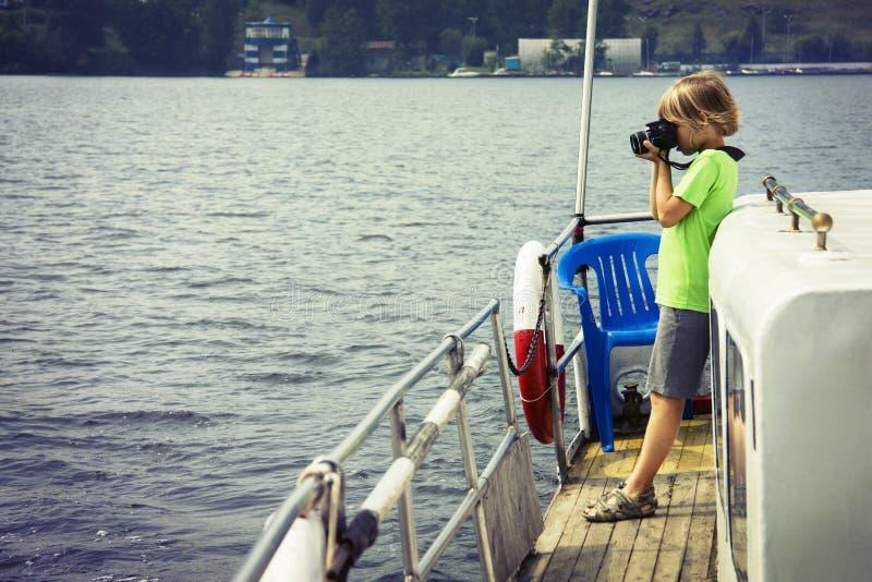 Мальчик на корабле фотографируя воду стоковая фотография