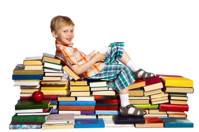 Мальчик на куче книг стоковые изображения