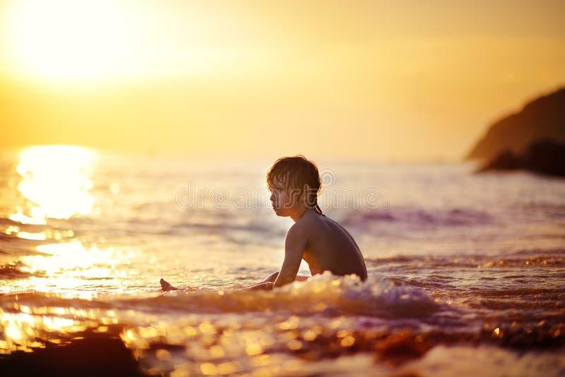 Мальчик на seashore на заходе солнца стоковая фотография